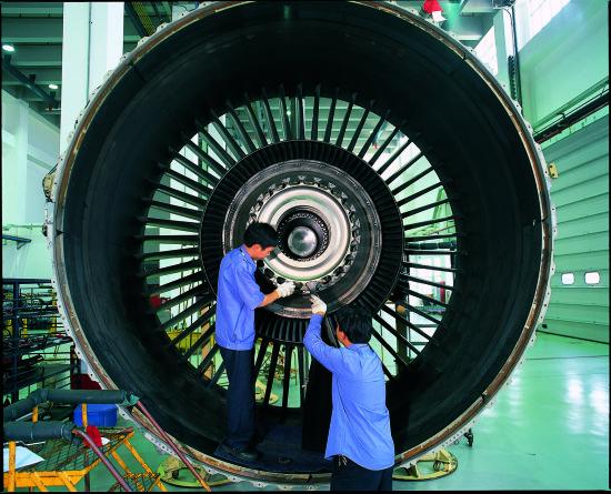 维修技术人员正在修理飞机发动机。